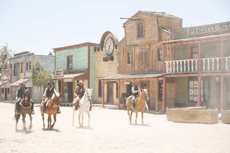 thespian: Gang of cowboys riding horses on wild west film set, Fort Bravo, Tabernas, Almeria, Spain