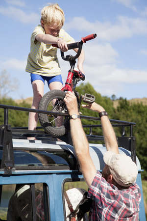Father removing BMX from top of off road vehicle, Lake Okareka, New Zealand LANG_EVOIMAGES