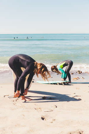Couple on beach, attaching surfboards to ankles