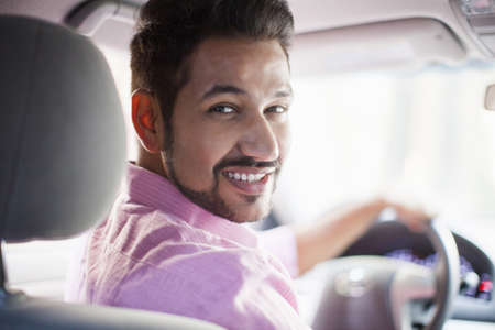 Portrait of young businessman looking over his shoulder in car