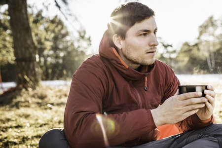 Young man sitting drinking coffee at lakeside LANG_EVOIMAGES