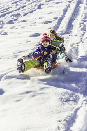 Girls riding sled down snow-covered slope, Achenkirch, Tirol, Austria LANG_EVOIMAGES