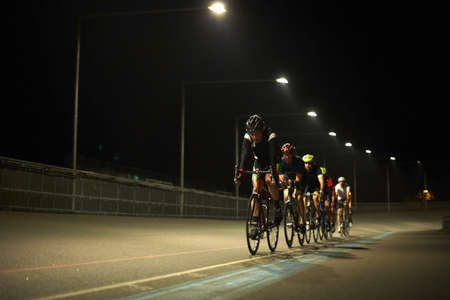 Cyclists cycling on track at velodrome, outdoors LANG_EVOIMAGES