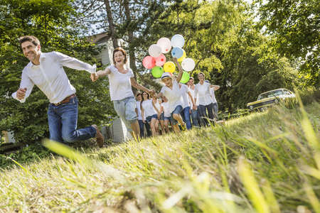 all under 18: Group of people running through forest, boy holding bunch of balloons