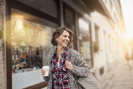 buen vivir: Mujer tomando un café mientras compras LANG_EVOIMAGES