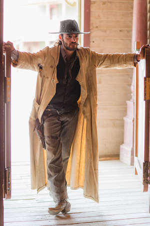 thespian: Cowboy standing in saloon doorway on wild west film set, Fort Bravo, Tabernas, Almeria, Spain LANG_EVOIMAGES