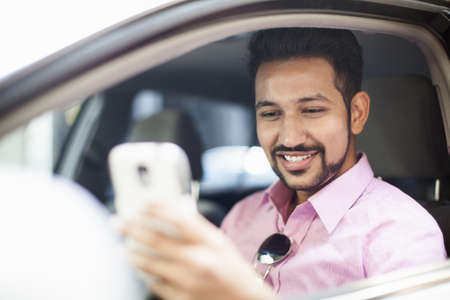 Young businessman reading smartphone text at car window