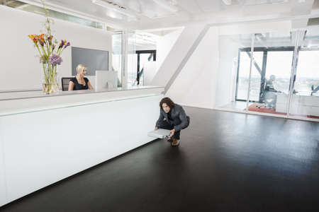 silliness: Man crouching in front of reception desk with briefcase LANG_EVOIMAGES