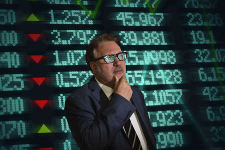 recuperating: Portrait of mature businessman with hand on chin in front of financial digital display