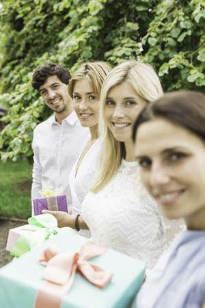 generosa: Retrato de hombre joven y tres mujeres con regalos de cumpleaños en el jardín