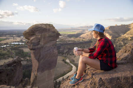 liberating: Young woman sitting gazing at view from top of Smith Rock, Oregon, USA LANG_EVOIMAGES