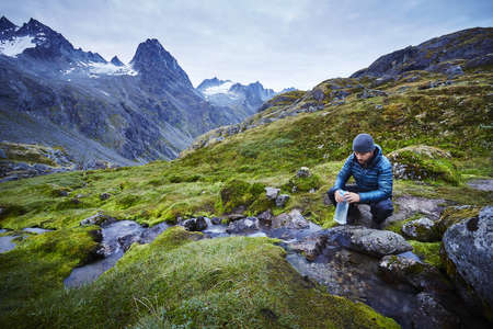 Male hiker filling water bottle from stream, Palmer, Alaska, USA