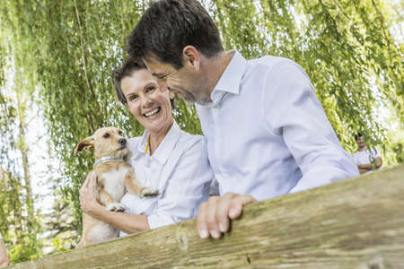 Portrait of couple with pet dog, standing by fence in forest