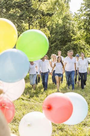 Group of people walking through forest, party balloons in foreground