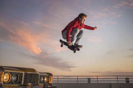 Portrait of young man on skateboard in mid air LANG_EVOIMAGES
