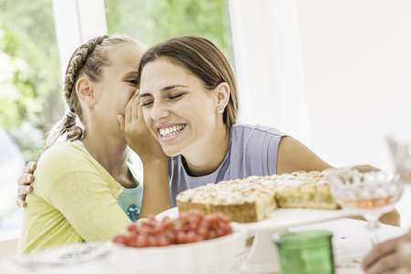 Girl whispering to mother at birthday party