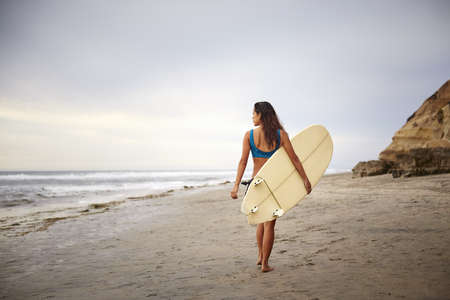 Rear view of young woman carrying surfboard strolling on beach, San Diego, California, USA LANG_EVOIMAGES