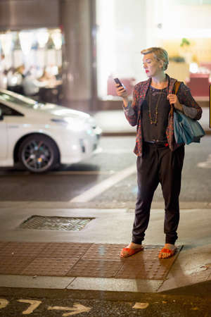 pantalones abajo: Mature woman texting on smartphone in the street at night, London, UK