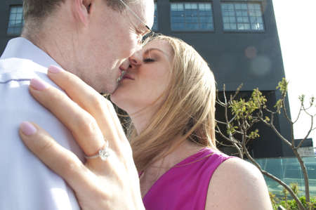 Couple kissing, woman wearing engagement ring
