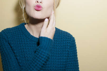puckered lips: Woman blowing kiss, partial view LANG_EVOIMAGES