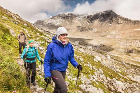 Three hikers hiking along path, Fil de Cassons, Segnesboden, Graubunden, Switzerland