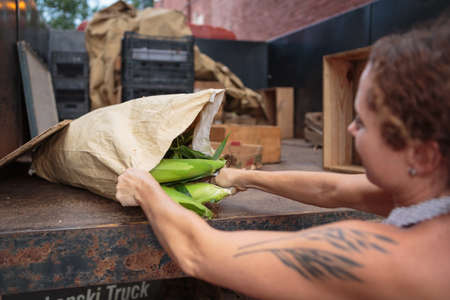 supermarket: Stall holder unloading sacks of organic food for store LANG_EVOIMAGES