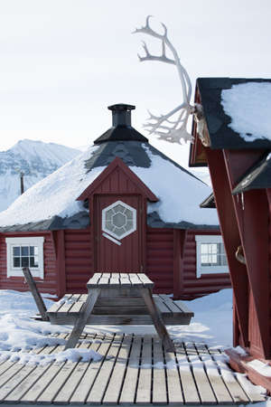 environmental issues: Traditional wooden house and picnic bench in snow, Longyearbyen, Svalbard, Norway