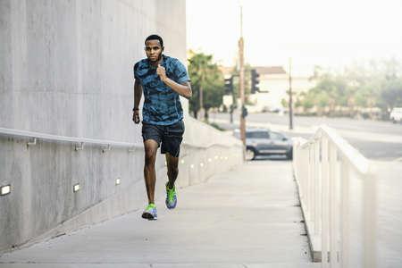 negative area: Young man running up city footbridge LANG_EVOIMAGES