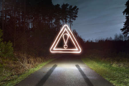 no skid: Tyre skid marks and glowing road warning sign above forest road at night