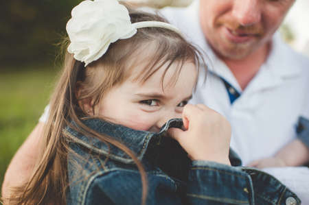 30 years old man: Young girl sitting with her father, hiding face with jacket