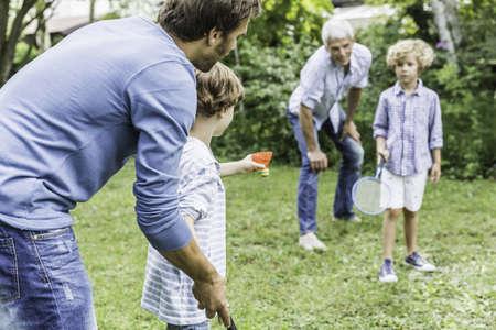 Mature man and son teaching grandsons badminton in garden