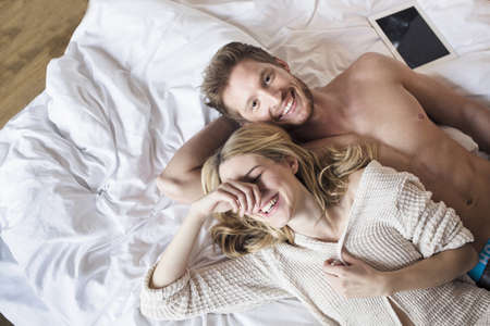 femme se deshabille: Young couple lying on bed in hotel room, laughing