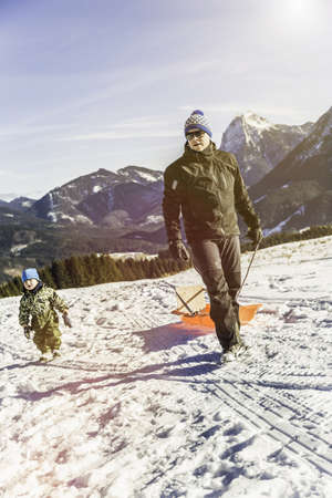 Man pulling sled on snow, Achenkirch, Tirol, Austria LANG_EVOIMAGES