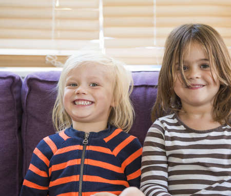 Portrait of young boy and girl, sitting on sofa, smiling