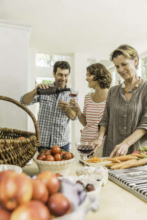 Three adults pouring red wine whilst preparing fresh vegetables