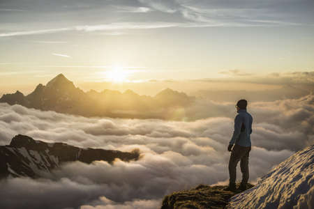 Young male mountain trekker looking at sunrise above clouds, Bavarian Alps, Oberstdorf, Bavaria, Germany