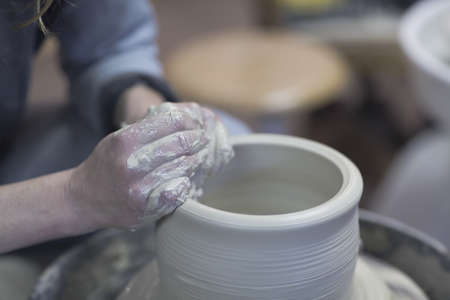 Close up of female potters hands forming clay pot on pottery wheel