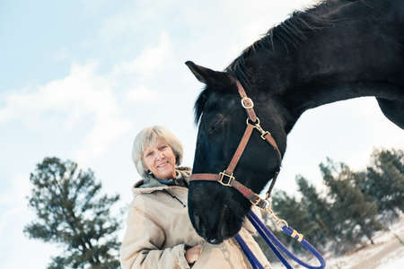 Senior adult woman standing with horse in snowy landscape
