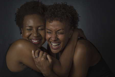 low self esteem: Studio portrait of two mature women hugging and laughing