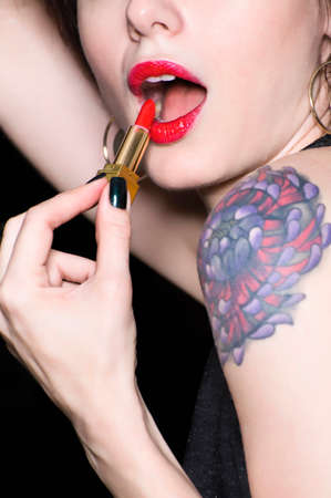 puckered lips: MId adult woman applying lipstick, mid section