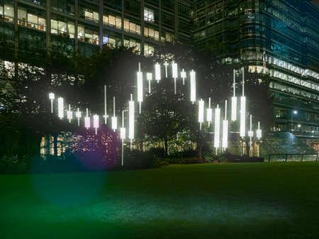 Tabla de comercio de estilo candelabro brillante frente a edificio de oficinas en la noche, Londres, Reino Unido