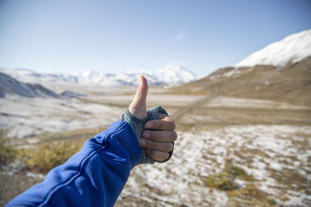 Young womans hand giving thumbs up, Mount Mckinley, Denali National Park, Alaska, USA