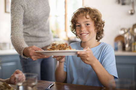 Mother serving spaghetti to children at dining table