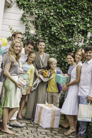 housing lot: Portrait of three generation family in garden with bouquet and birthday gifts LANG_EVOIMAGES
