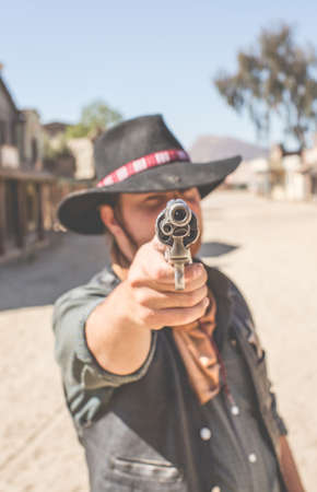 thespian: Cowboy pointing handgun on wild west film set, Fort Bravo, Tabernas, Almeria, Spain LANG_EVOIMAGES