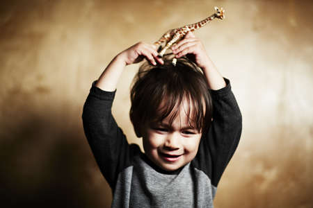 Portrait of cute male toddler holding toy giraffe on his head