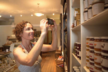reminding: Mid adult woman photographing preserves on smartphone in organic grocery