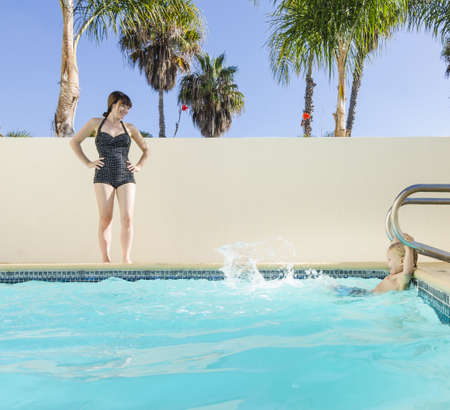 Mother watching son splashing in swimming pool, Los Angeles, California, USA