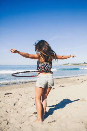 tummy time: Woman using hula hoop on beach, rear view LANG_EVOIMAGES