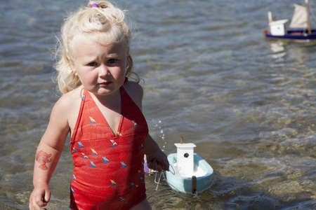 Portrait of girl puling toy boat, Lake Okareka, New Zealand